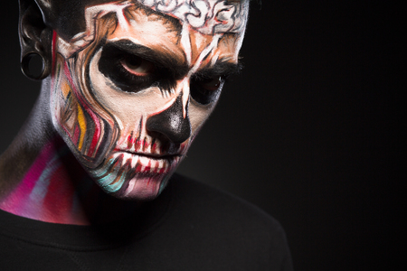 close up eyes: Close up portrait of man with colored skull make up. Face art, male with scary face isolated on black background.