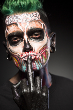 close up eyes: Skull face art, mystical makeup on mans face. Man with skeleton face showing long finger on black palm.