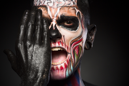 close up eyes: Halloween makeup concept, man covering zombie face with black painted hand. Detailed portrait of mans face with colores skeleton face. Stock Photo