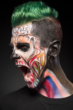 close up eyes: Mystical face art, scary skeleton man with open mouth showing teeth. Monster makeup on mans face. Stock Photo