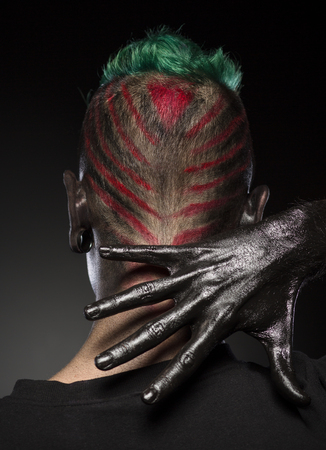 close up eyes: Hair style for Halloween party. Rear view of man with skull makeup and hair colored in bright colores.