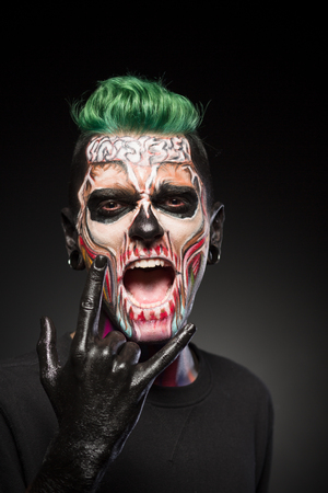 close up eyes: Man with halloween makeup showing tongue. Stylish zombie makeup on mans face, isolated in black background. Stock Photo