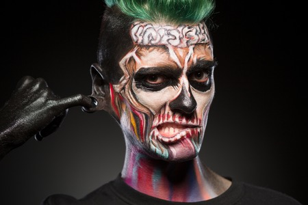 close up eyes: Skull face art, portrait of man with bright mystical makeup. Zombie mask on mans face isolated in black background.