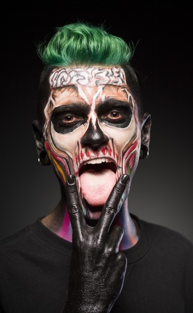 close up eyes: Face art, man with green hair and bright skull makeup showing tongue. Halloween makeup, dead face in color.