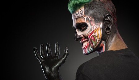 close up eyes: Side view of a man with monster face make up and hand painted in black. Mystical face art, man with skull makeup.