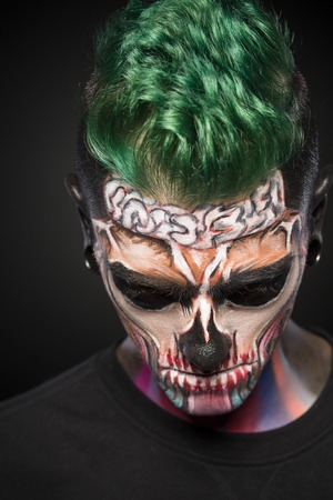 close up eyes: Front view of man with green hair and colored skull makeup. Professional makeup for Halloween. Stock Photo