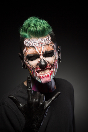 close up eyes: Young man with scary skeleton face. Face art, colored zombie face for Halloween. Stock Photo