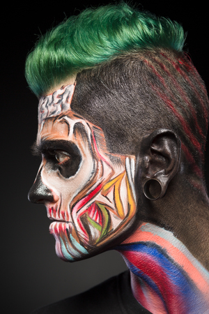 close up eyes: Side view portrait on man with zombie face art in bright colores. Scary zombie makeup for Halloween.
