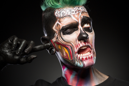 close up eyes: Face art concept, briht skull makeup on mans face. Zombie man touching ear with palm painted in black.
