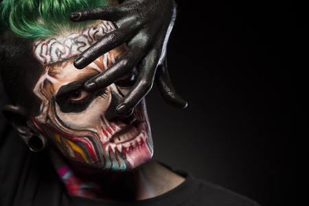 close up eyes: Bight makeup for Halloween party. Mans face with colored skull makeup, covering face with hand painted in black. Stock Photo
