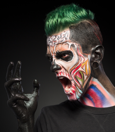 close up eyes: Professional fashion skull makeup. Fantasy art makeup on mans face isolated on black background. Stock Photo