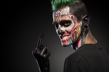 close up eyes: Side view if a man with colored skull makeup showing long finger. Face art, man with zombie face.