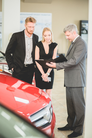 Family couple buying new car, talking with vehicle dealer. Sales manager at auto dealership selling car to young man and woman. Stock Photo