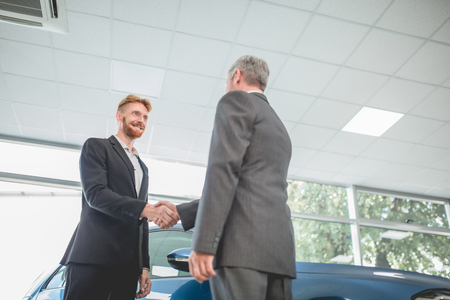 Handsome man shaking hand with vehicle seller. Car showroom, man purchasing new car. Stock Photo
