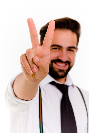 Hansome stylish brunette man showing victory with fingers. Close up view of young happy businessman.