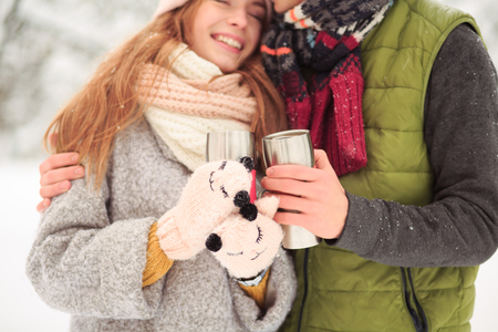 Frosty weather. Adults have some hot drink outside. Stock Photo