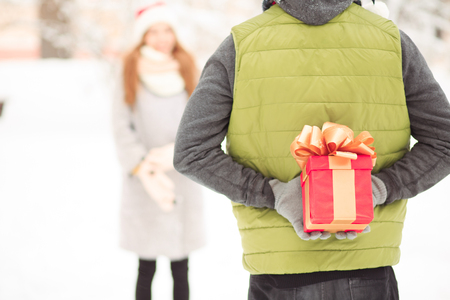 A boy hides a present behind his back. A girl is looking forward to it.