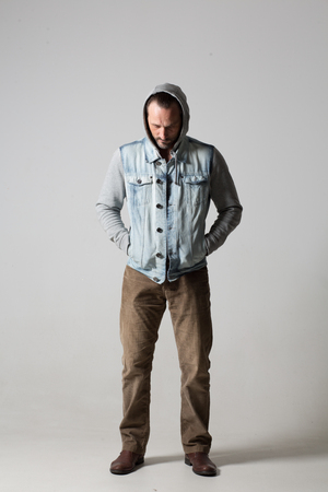 Young man in hoodie and sleeveless jeans jacket standing on white background. 版權商用圖片