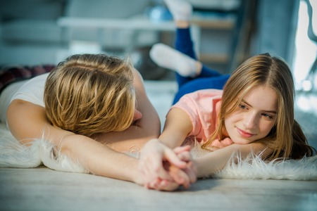 Young lovers relaxing together by holding the hands. A boy is passionately looking at his lady love.