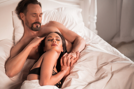 Adult couple in bed. Man gently touching her hair. Stock Photo