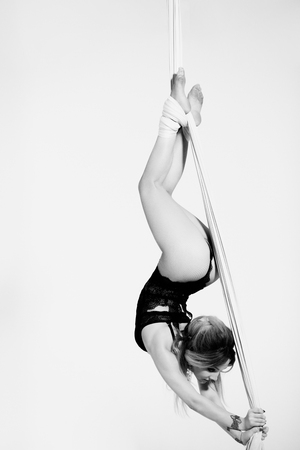 Alluring female acrobatics. Flying in air on silk tissue.