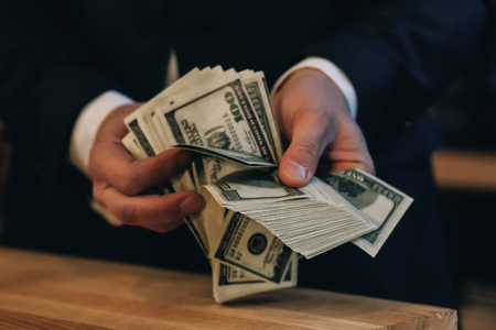 Man in black suit counting dollars at wooden desk.