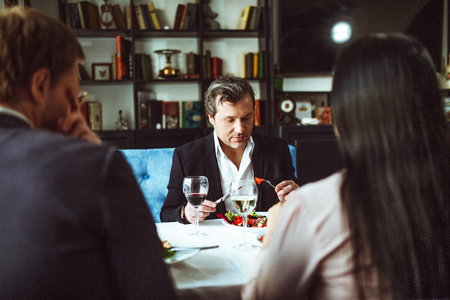 Two men and one woman having business lunch. Having business conversation. Stock Photo