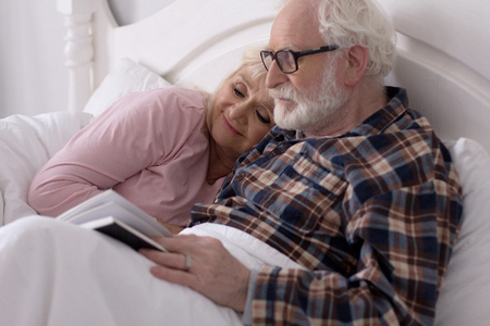 Senior couple having rest in their bedroom looking through magazine. Sweet elderly lady with white hair hugging her husband before bedtime. Reklamní fotografie