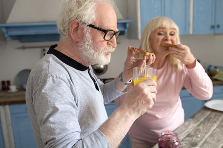 Old grandpa chewing on some jam toasts with his wife at breakfast. Cute old man with glasses and white beard having some bread with jelly and orange juice for meal with his wife.