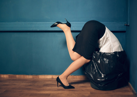 Woman trying to get her head out of garbage basket. Lady dressed in business casual clothes got her head stuck in black trash can. Reklamní fotografie - 103677982