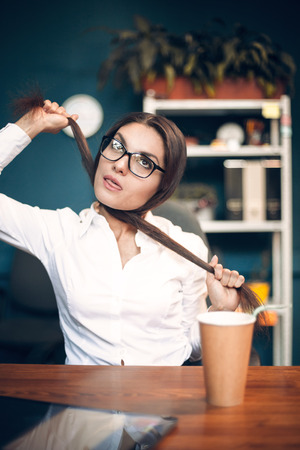 Beautiful mad woman choking herself with her hair. Crazy female office worker with glasses wearing white blouse strangling herself with her long brown hair while sitting at office table.