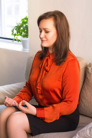 Beautiful woman meditates at home on couch. Portrait of young beautiful female in orange shirt sitting on sofa relaxing and meditating. Stock fotó