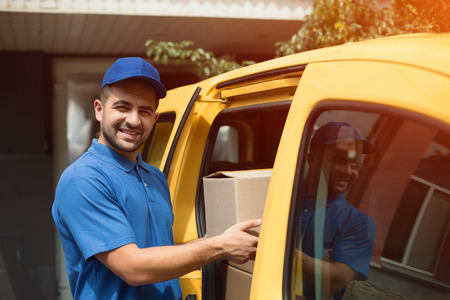 Delivery man getting package out of van. Young delivery guy wearing light blue uniform standning next to yellow van and getting big cardboard box out.