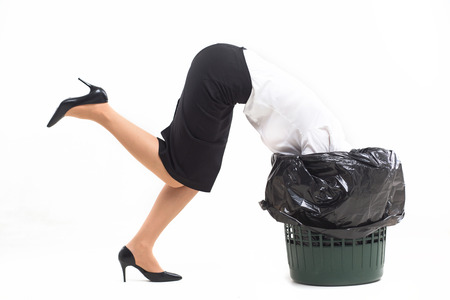 Woman getting stuck in trash can with her head. Crazy woman wearing white blouse black skirt and black heels got stuck in bucket for trash.