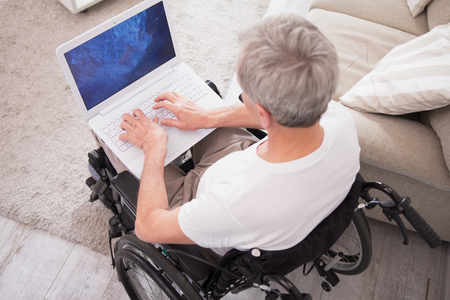 Man in wheelchair typing on laptop. Top view of elderly disabled man with gray hair using computer while sitting in wheelchair.