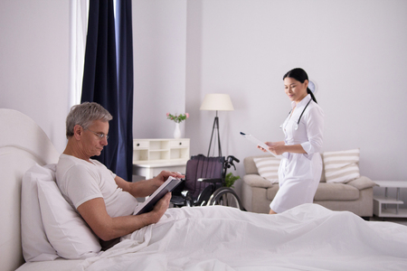 Old man sitting in his bed reading book with nurse in room. Pretty asian caregiver came into room to check up on elderly disabled patient.