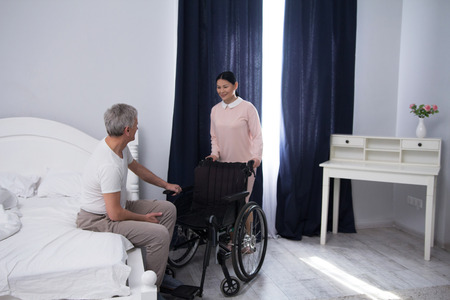 Nurse bringing wheelchair to patient. Beautiful asian caregiver pushing wheelchair to bed on which elderly man is sitting.