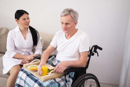 Nurse sitting next to man while he is eating. Beautiful asian lady watching after aged man who is having lunch on food tray while sitting in wheelchair.