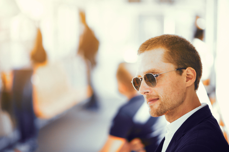 Businessman in metro. Handsome man in suit and sunglasses sitting on subway train. People blurred in background.