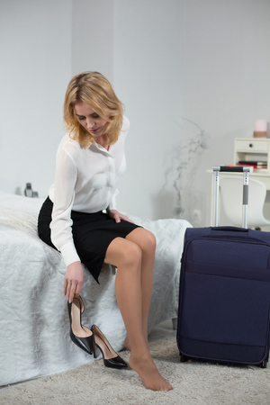 Young businesswoman in fashion clothes taking off high heel shoes. Tired after working day.