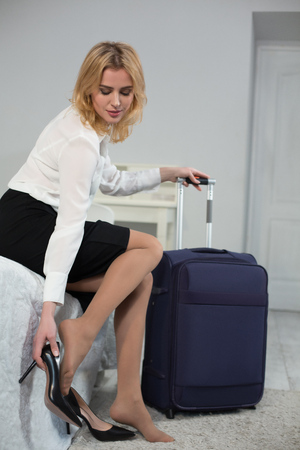 Beautiful businesswoman sitting on sofa and taking off high heel shoes. Holding big suitcase by other hand.