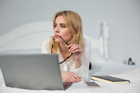 Businesswoman lying in bed and looking aside. Having laptop n front of. Business in bed concept.