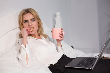 Nice businesswoman having coffee and buscuits in bed. Relaxing while working.