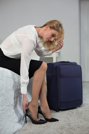 Businesswoman taking off fashion high heel shoes. Came back after business trip.