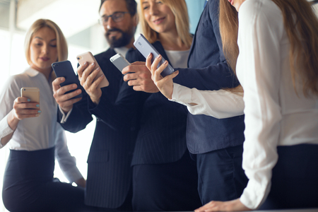 Businessteam exchanging information by using phones. being in modern office. Business concept. Stock Photo