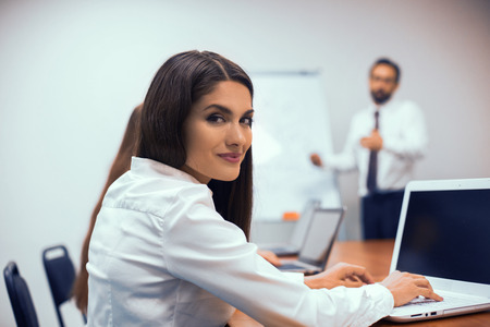 Brunette woman sitting at desk i negotiating room. Listen to colleague who giving presentation.