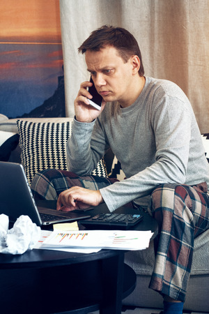 Young busy father in pyjamas sitting on sofa and working on laptop while speaking over phone.
