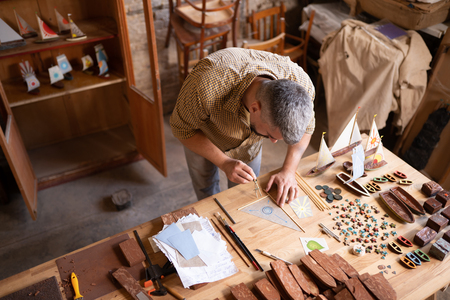 Concentrated carpenter at his working table. A man in his workshop works on drawing a sail of a ship