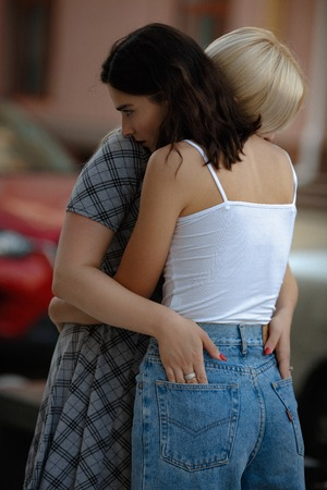Two young beautiful lesbians hugging each other in the street. Samesex love concept.