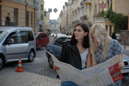 Two charming cheerful women looking for some city plcaes on map. Having romantic day. Lesbian love concept. Stok Fotoğraf